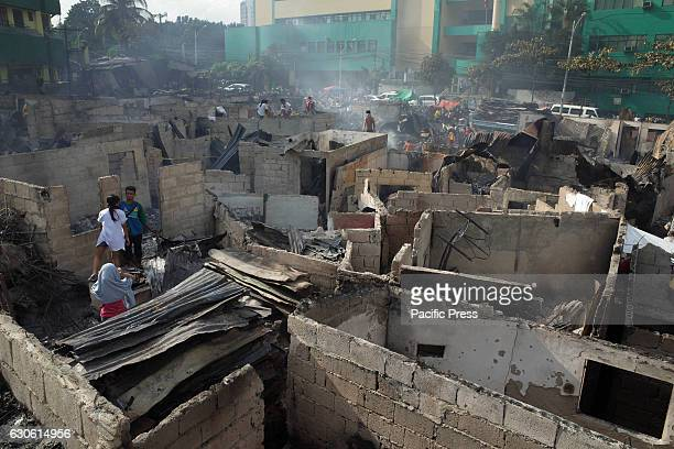 Filipinos looks for salvageable materials following a fire at an informal settler colony in Quezon City, east of Manila on Wednesday. According to...