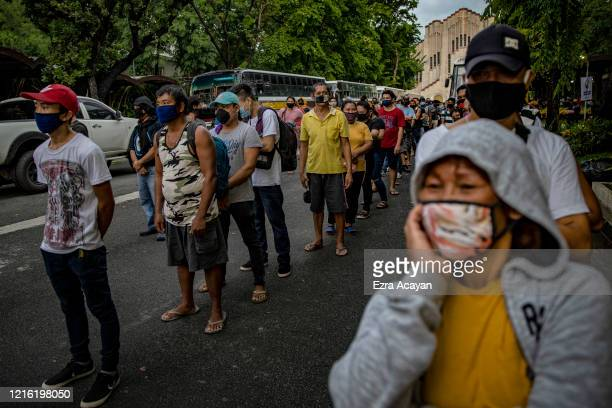 Filipinos out of work and stranded due to the coronavirus pandemic queue to receive meals before taking a free bus ride home to their province on May...