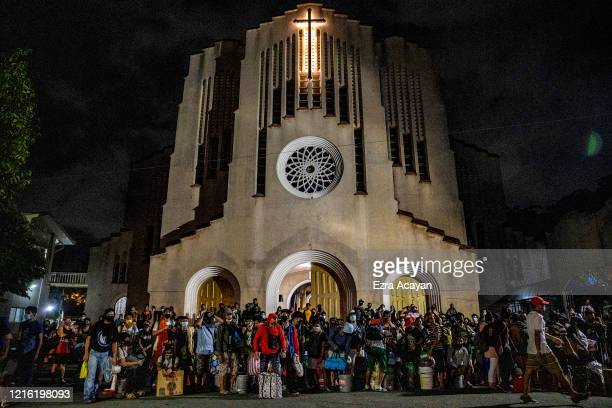 Filipinos out of work and stranded due to the coronavirus pandemic queue outside a church as they wait for a free bus ride home to their province on...