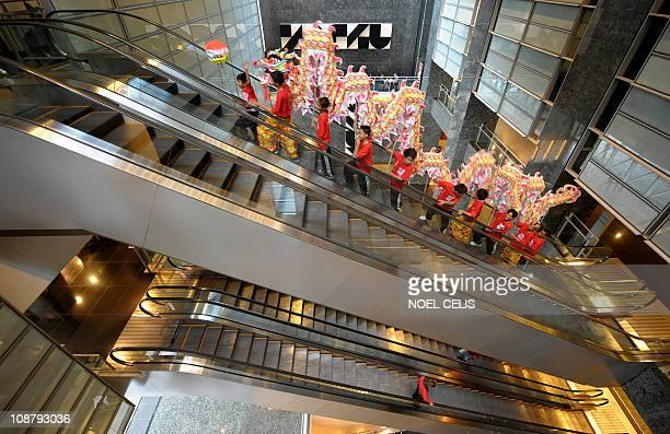 Filipinos performers taking part in a dragon dance use an escalator at the Philippine Stock Exchange in Manila on February 3 2011 as the institution...