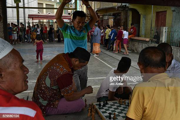 Filipinos play a game of chess while others queue to cast their vote at a polling precinct on May 9 2016 in Davao city Philippines Voters in the...