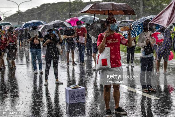 Filipinos stand in the rain as they take part in a protest against President Duterte's AntiTerror bill on June 12 2020 in Quezon city Metro Manila...