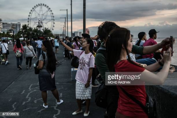 Filipinos takes pictures during sunset in Manila on April 26 2017 Firebrand Philippine President Rodrigo Duterte is set to enjoy muchwanted foreign...