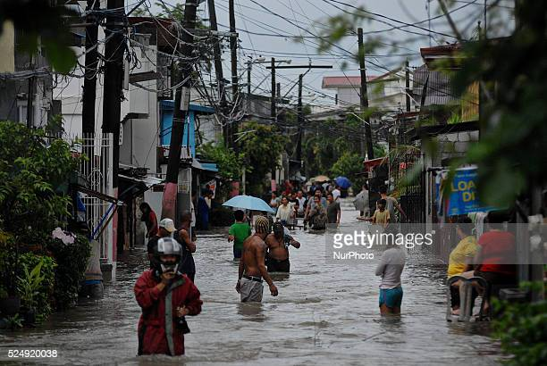 Filipinos wade through floodwater in Kawit township Cavite province Philippines August 19 2013 Tropical Storm Trami intensified as it continued to...