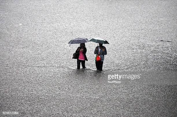 Filipinos wade through floodwater in Manila Philippines August 20 2013 Heavy rains intensified by tropical storm Trami continued for a second day...