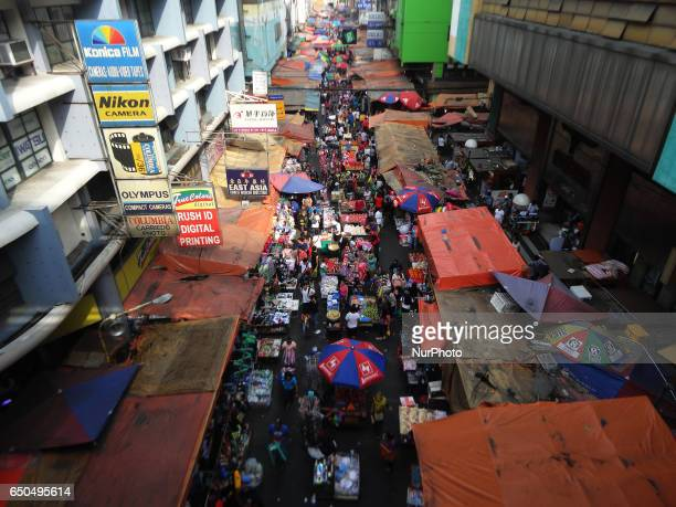 Filipinos walk through a marketplace in Manila Philippines on Thursday March 9 2017