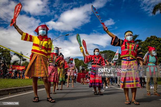 Filipinos wearing face masks and face shields to protect against COVID-19 take part in an anti-government protest on November 30, 2020 in Quezon...