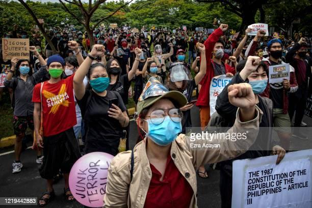 Filipinos wearing face masks take part in a protest against President Duterte's AntiTerror bill on June 12 2020 in Quezon city Metro Manila...