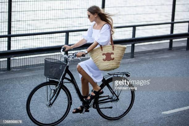 Filippa Haegg is seen on her bike wearing white dress, Celine basket bag, Chanel sandals during Stockholm Fashion Week Digital Edition 2020 on August...