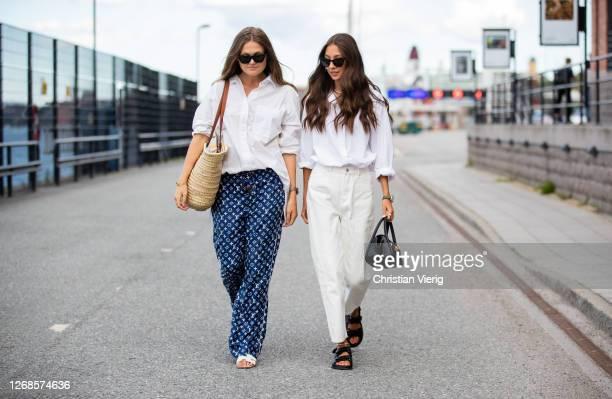 Filippa Haegg is seen wearing blue Louis Vuitton pyjama pants, white blouse, Celine basket bag and Felicia Akerstrom wearing white blouse and pants,...
