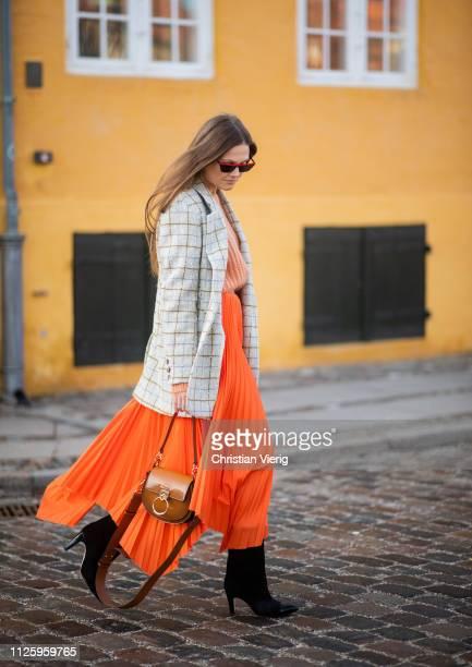 Filippa Haegg is seen wearing brown Chloe bag black boots orange skirt knit checked blazer jacket outside Resume during the Copenhagen Fashion Week...