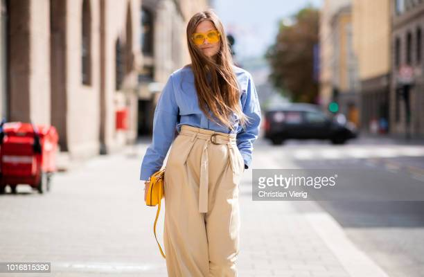 Filippa Haegg wearing beige high waisted pants yellow bag yellow sunglasses blue shirt is seen outside Epilogue during Oslo Runway SS19 on August 14...