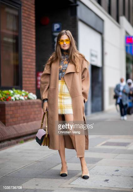 Filippa Haegg wearing beige wool coat yellow checked skirt is seen outside Natasha Zinko during London Fashion Week September 2018 on September 18...