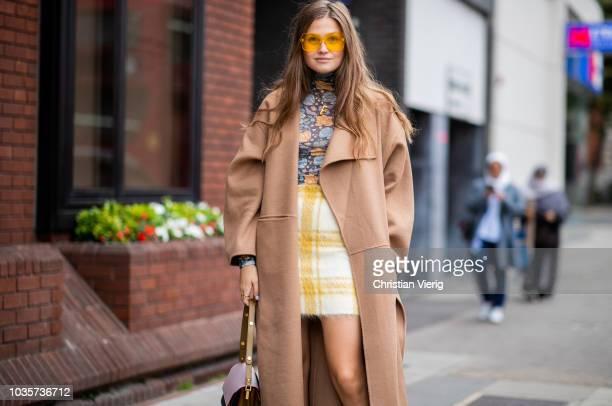 Filippa Haegg wearing beige wool coat yellow checked skirt is seen outside Natasha Zinko during London Fashion Week September 2018 on September 18...