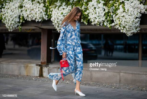 Filippa Haegg wearing blue white dress red mini Hermes bag white shoes is seen during Stockholm Runway SS19 on August 28 2018 in Stockholm Sweden