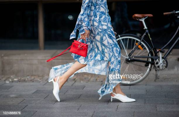 Filippa Haegg wearing blue white dress red mini Hermes bag white shoes is seen during Stockholm Runway SS19 on August 28 2018 in Stockholm Sweden