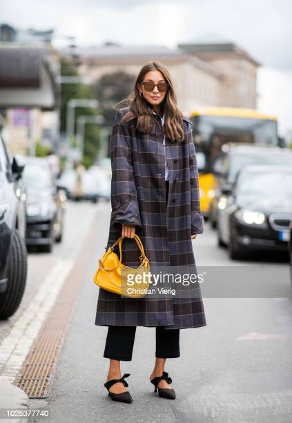 Filippa Haegg wearing checked coat yellow bag during Stockholm Runway SS19 on August 30 2018 in Stockholm Sweden
