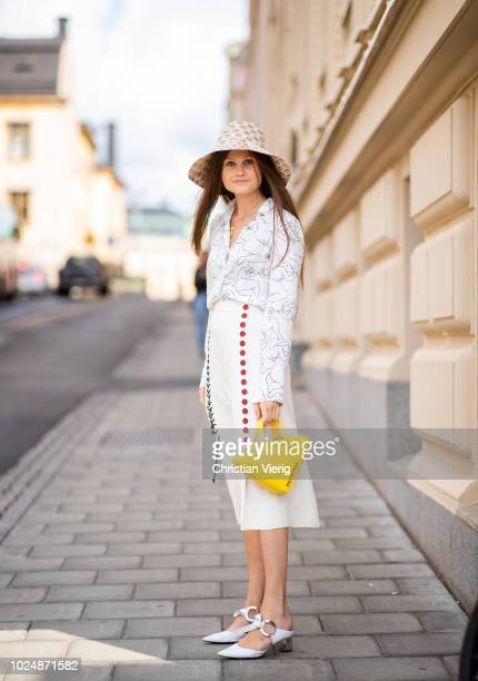 Filippa Haegg wearing Gucci bucket hat yellow Balenciaga triangle bag blouse with print midi skirt with slit seen during Stockholm Runway SS19 on...