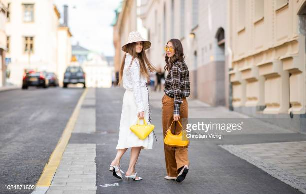 Filippa Haegg wearing Gucci bucket hat, yellow Balenciaga triangle bag, blouse with print, midi skirt with slit and Felicia Akerstrom Ma wearing...