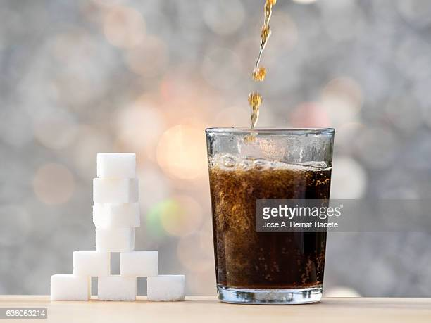 Fill a glass of refreshment of tail sweetened, with his equivalent close to the glass in cubes of sugar