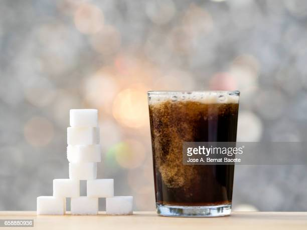 Fill a glass of refreshment of tail , with his equivalent close to the glass in cubes of sugar
