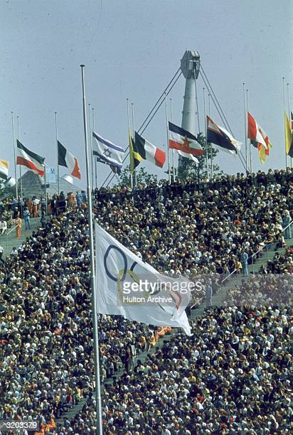 Filled bleachers at a memorial service for the slain Israeli athletes at the Olympic Games, with national and Olympic flags at half-mast, Munich,...
