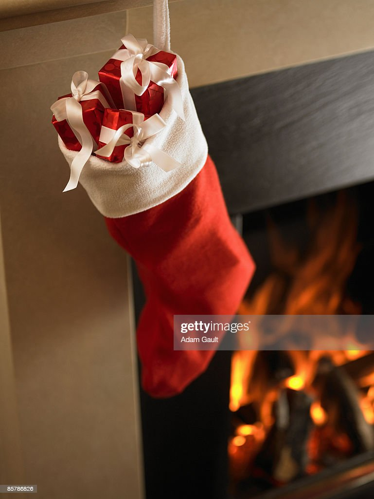 Filled Christmas Stocking Hanging by the Fire : Stock Photo