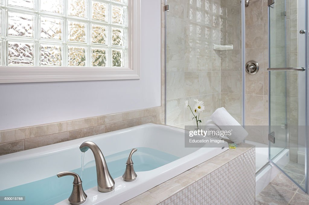 Filled soaking tub next to glass shower Pictures | Getty Images