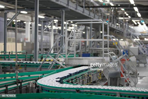 Filled softdrink cans pass along a conveyor inside the Refresco Group NV beverage bottling factory in Maarheeze Netherlands on Thursday Oct 5 2017...