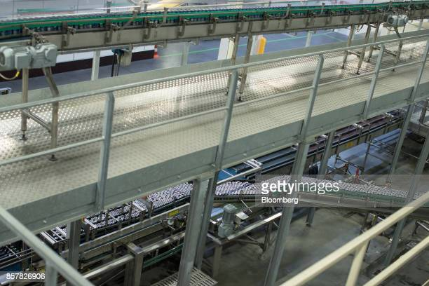 Filled softdrink cans pass along conveyors inside the Refresco Group NV beverage bottling factory in Maarheeze Netherlands on Thursday Oct 5 2017...