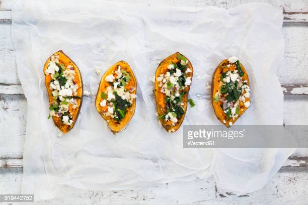 filled sweet potato with spinach, red onion, couscous, feta and coriander - wax paper stock photos and pictures