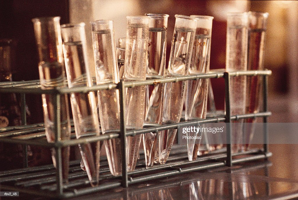 filled test tubes sit in a black rack on a reflective table in a science lab : Foto de stock