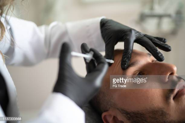 filler injection for male face in beauty clinic - botox stock pictures, royalty-free photos & images