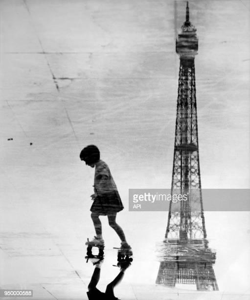 Fillette faisant du patin à roulettes à côté du reflet de la Tour Eiffel en 1920 à Paris France