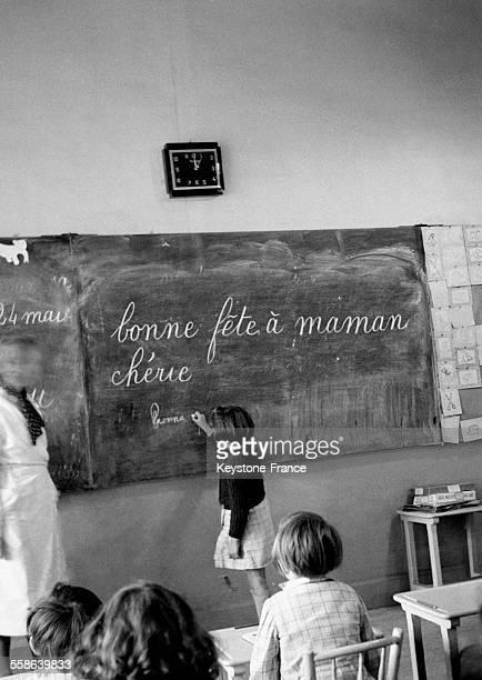 Fillette recopiant sur un tableau d'école un message pour la fête des mères qui vient d'être officiellement instaurée dans le calendrier français par...