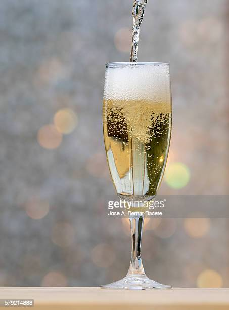 Filling a glass of champagne on a table iluminanada for the light of the Sun