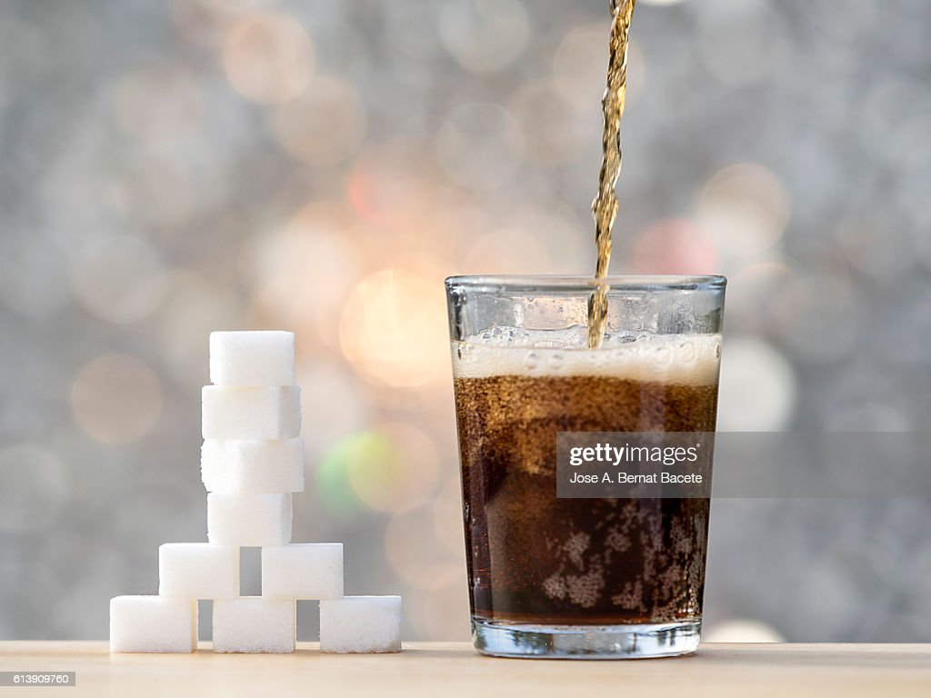 Filling a glass with cola and its equivalent in sugar cubes : Stock Photo