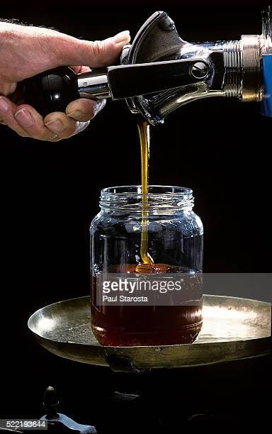 Filling a jar of honey