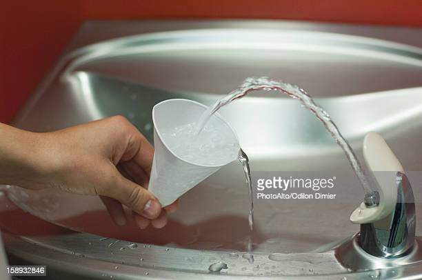 Filling cup at drinking fountain, cropped