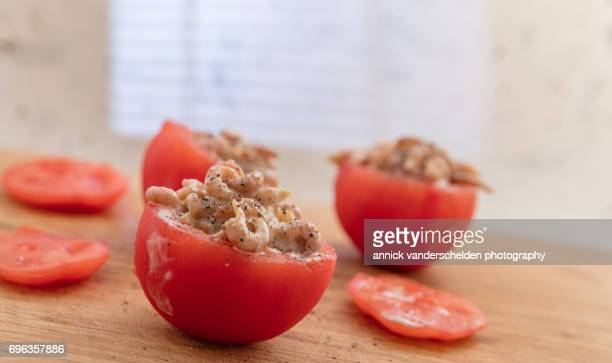Filling hollowed-out tomatoes with shrimp mixture.
