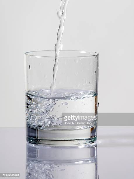 Filling of a glass of glass water on a white bottom