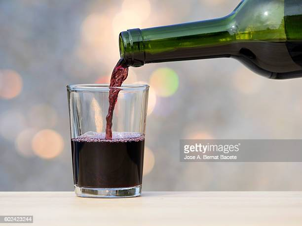 Filling of one glass of stained wine for a bottle of crystal, illuminated by the light of the Sun.