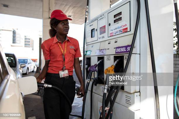 A filling station attendant fills a car with fuel at a petrol station on July 30 2018 in Harare Zimbabwe Zimbabweans went to the polls today to vote...