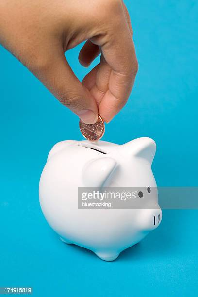 filling the piggy bank - us penny stock pictures, royalty-free photos & images
