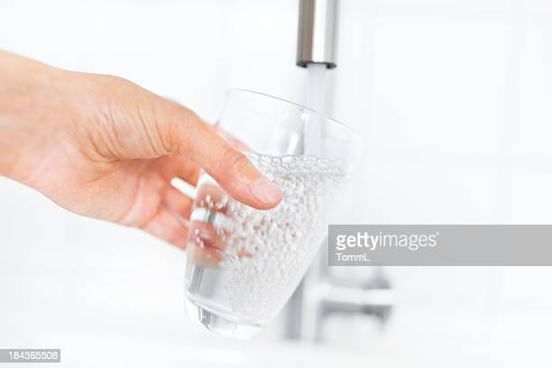 Filling up a clear glass of water