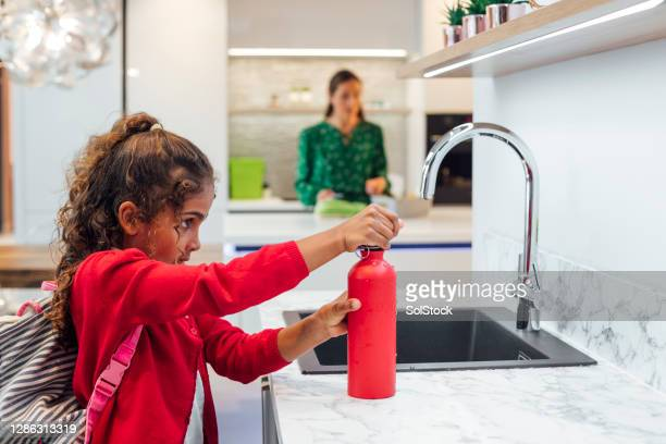 filling up water bottle - water stock pictures, royalty-free photos & images
