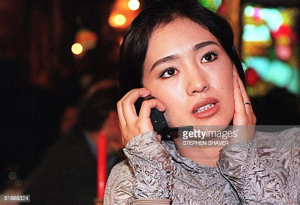 Film actress Gong Li toast covers her ear as she talks on a mobile phone 08 October at a private reception with famous Chinese film director Chen...