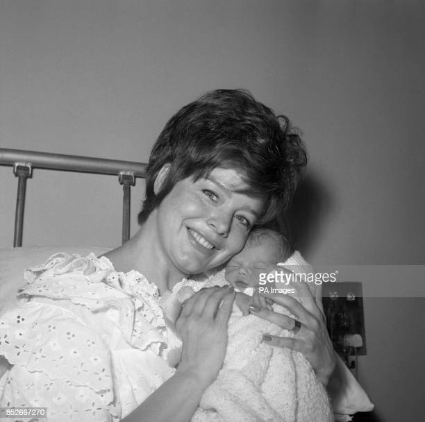 Film actress Janet Munro gently clasps her baby daughter Sally at her maternity home in Woking The baby weighed 6klbs