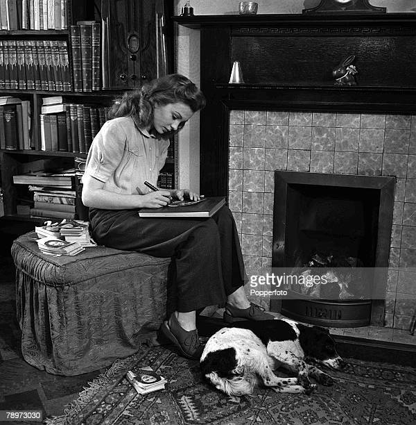 Film actress Jean Simmons signing autographs on photographs for her fans as she sits at the fireplace with her pet dog at home 28th February 1946
