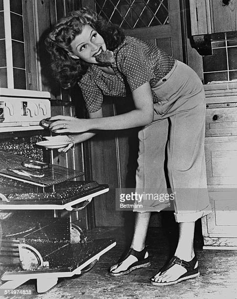 Film actress Rita Hayworth enjoys a snack fresh from the oven